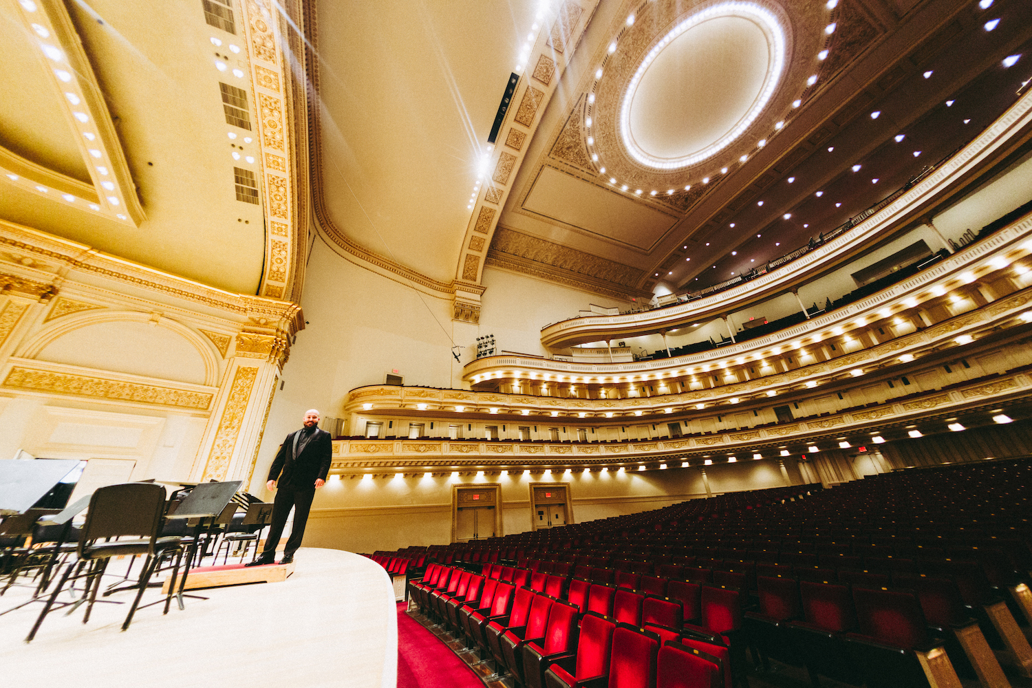 WE.LSU.CARNEGIE.GioOnstage – The La Sierra University Wind Ensemble Director Giovanni Santos pauses for a photo on the Isaac Stern Auditorium/Ronald O. Perelman Stage at Carnegie Hall.