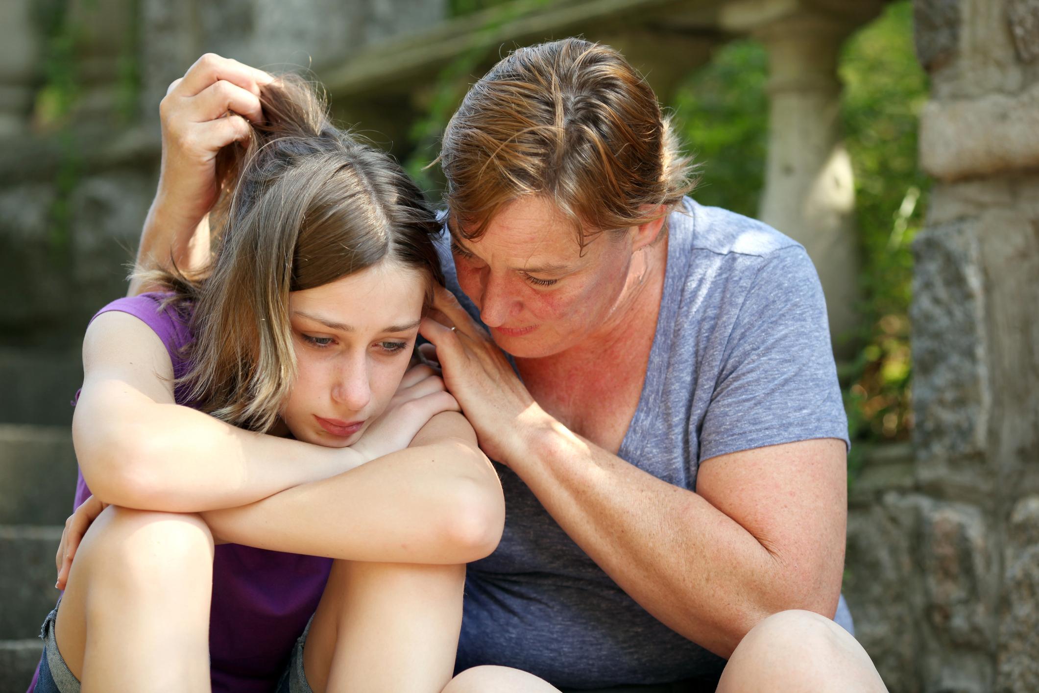mom comforts teen daughter