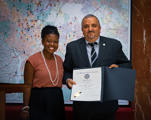 State assemblywoman Jheanelle Wilkins presents Imad Madanat, vice president for programs at ADRA International, with an official citation for ADRA's refugee work from the state of Maryland.