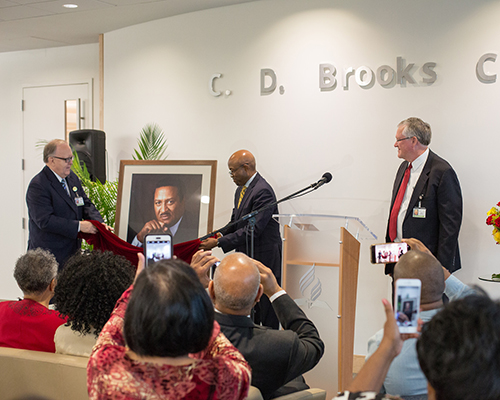Dan Jackson, NAD president, Alex Bryant, NAD executive secretary, and Ken Denslow, executive assistant to the president of NAD, unveil a portrait during the C.D. Brooks Prayer Chapel Dedication Ceremony.