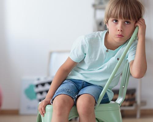 Sad boy in chair ADHD