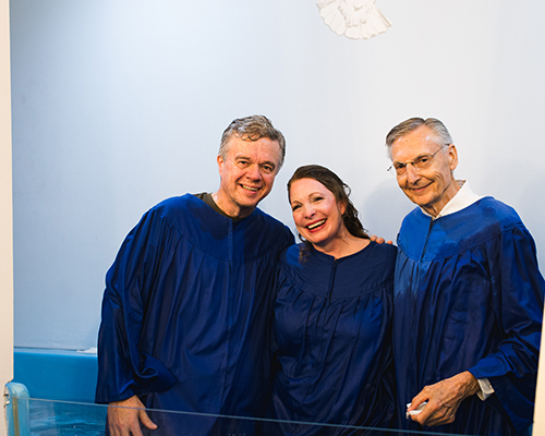 Hayes and Paige Parnell (left – center) smile alongside Pastor Edward Skoretz (right) after their baptism at Summerville Seventh-day Adventist Church in Summerville, Georgia.